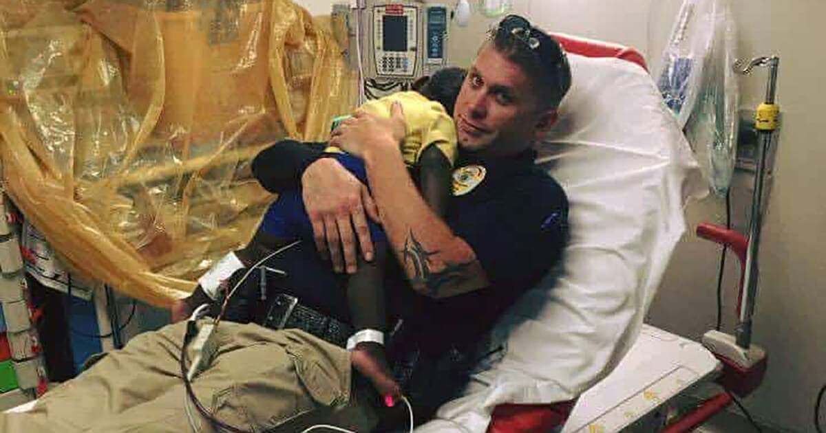 A picture of a cop curling up with an abandoned toddler has become viral - look closely and you'll understand why